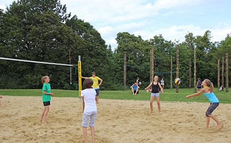 Gruppe spielt Beachvolleyball