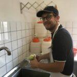 Bild von David beim Salarschneiden in der Spülküche.