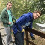 Bild von Raphael und David beim Streichen eines Holzgeländers.