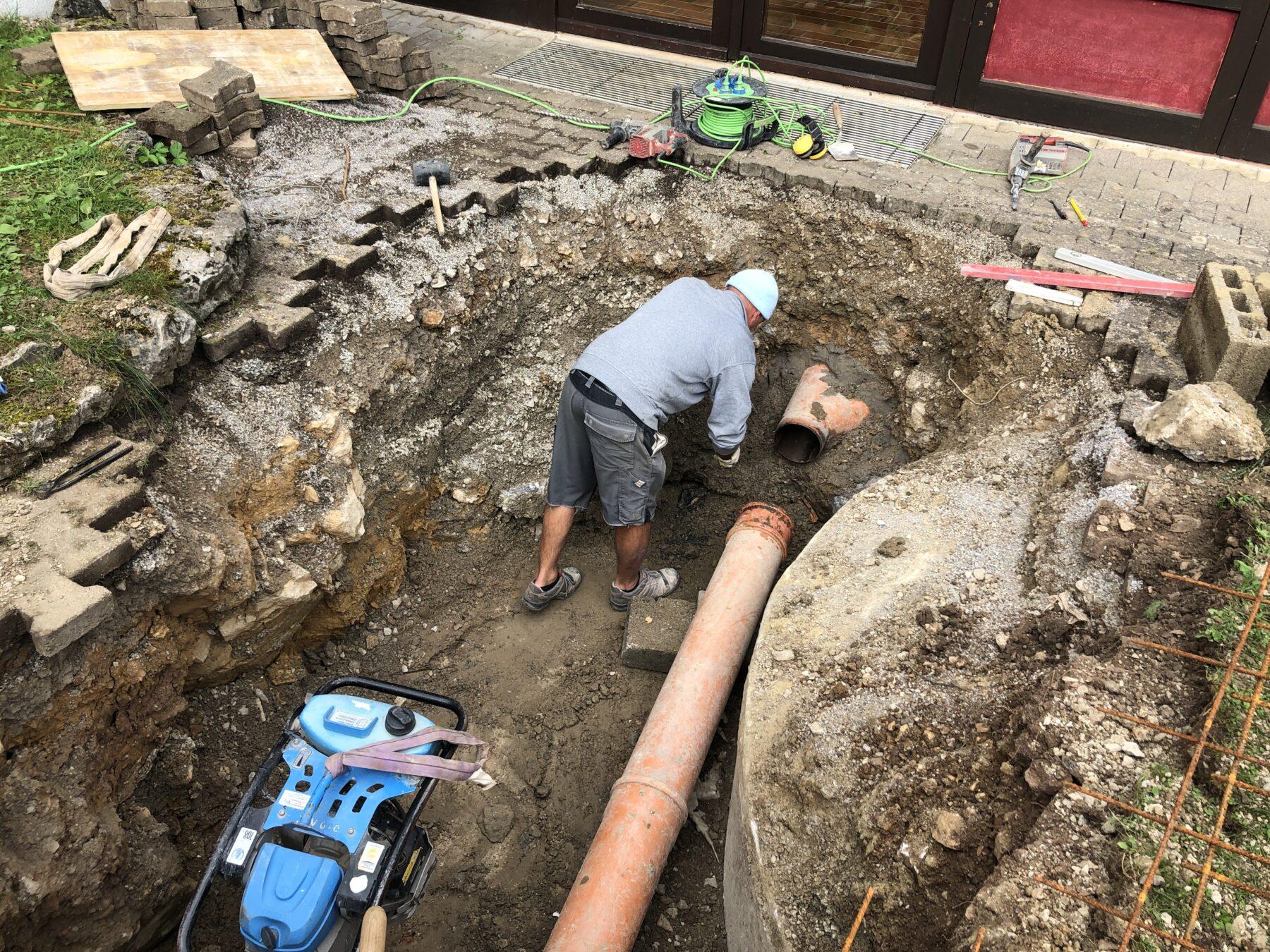 Bild: Arbeiter steht in der Baugrube und repariert die Abwasserleitung.